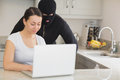 Woman using laptop while burgler is watching in kitchen Stock Photos