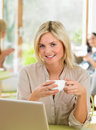 Woman using laptop in cafe busy Royalty Free Stock Image