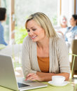 Woman using laptop in cafe enjoying drink smiling to camera Stock Images