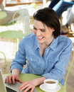 Woman using laptop in cafe smiling Stock Photography