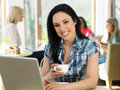 Woman using laptop in cafe smiling to camera Royalty Free Stock Photography