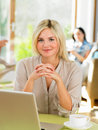 Woman using laptop in cafe smiling to camera Stock Image