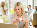 Woman using laptop in cafe smiling to camera Stock Photo