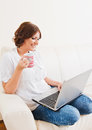 Woman using laptop and drinking from a mug on the sofa Royalty Free Stock Photography