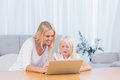 Woman using laptop with her daughter in the living room Royalty Free Stock Image