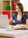 Woman using a laptop at home photo of beautiful drinking coffee and reading book Royalty Free Stock Photo