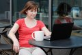 Woman using laptop in a outdoor cafe drinking coffee and Stock Photography