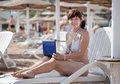 Woman using  laptop at resort beach Stock Photo
