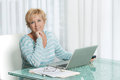 Woman using laptop to work from home middle aged talking on phone and working on a Royalty Free Stock Images