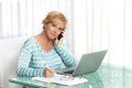 Woman using laptop to work from home middle aged talking on phone and working on a pen in hand Stock Photo