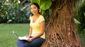 Woman using a laptop young sitting near tree Royalty Free Stock Images