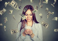 Woman using looking at her smart phone under money rain