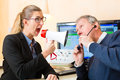 Woman using a loudhailer in hearing test older men or pensioner with problem make and may need aid Royalty Free Stock Photography