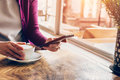 Woman using mobile phone in cafe female holding cup coffee and Royalty Free Stock Images
