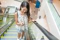 Woman using mobile phone on escalator Royalty Free Stock Photo