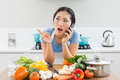 Woman using mobile phone in front of vegetables in kitchen young the at home Stock Images