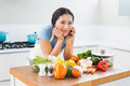 Woman using mobile phone in front of vegetables in kitchen young the at home Stock Image