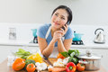 Woman using mobile phone in front of vegetables in kitchen young the at home Stock Photography