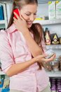 Woman using mobile phone while looking at product young in supermarket Stock Image