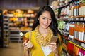 Woman using mobile phone while shopping for grocery Royalty Free Stock Photo