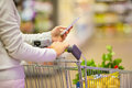 Woman using mobile phone while shopping in supermarket female store cell close up Stock Photography