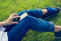 Woman using mobile smart phone on the legs in green grass Royalty Free Stock Photo