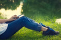 Woman using mobile smart phone on the legs in green grass and lake Royalty Free Stock Photo