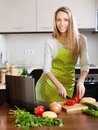 Woman using notebook during cooking vegetables happy at home kitchen Royalty Free Stock Image