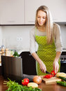 Woman using notebook during cooking vegetables at home Stock Image