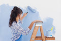 Woman using paint roller to paint wall in blue leaning on ladder Royalty Free Stock Photography
