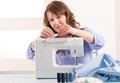 Woman using sewing machine beautiful young at home and changing reel of thread focus on Stock Photos
