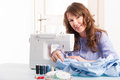 Woman using sewing machine beautiful young at home with reels of thread pins buttons and thimble Stock Image
