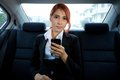Woman using a smart phone beautiful young business asian in car Stock Photography