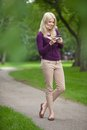 Woman using smart phone in park full length of a happy young Royalty Free Stock Photos