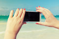 Woman using smart phone for taking outdoor photo on a beach in dominican republic vintage style filter effect Stock Images