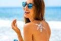 Woman using sun cream on the beach Royalty Free Stock Photo