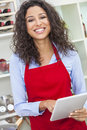 Woman using tablet computer cooking in kitchen a beautiful happy young or girl wearing a red apron a while her at home Royalty Free Stock Image