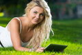 Woman using tablet outdoors lying on grass with digital Royalty Free Stock Image