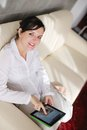 Woman using tablet pc at home young relaxing in her lliving room reading a digital surf internet and work Stock Photos