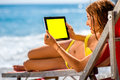 Woman using tablet on the sunbed young in yellow swimsuit holding digital with empty screen lying red beach Stock Photos