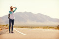 Woman On Vacation Hitchhiking Along Road Using Mobile Phone Royalty Free Stock Photo