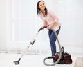 Woman vacuum cleaning carpet young cheerful brunette in home interior Stock Photo