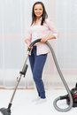 Woman vacuum cleaning carpet young cheerful brunette in home interior Royalty Free Stock Images