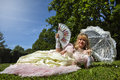 Woman in venetian costume lying on the green park with white umbrella period ground a ith blu sky and trees background Stock Photography
