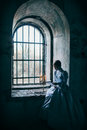 Woman in victorian dress imprisoned a dungeon Royalty Free Stock Image
