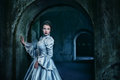Woman in victorian dress imprisoned a dungeon Stock Image