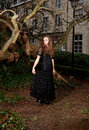 Woman in victorian dress in the park a black front of a house and trunks of trees Royalty Free Stock Photo