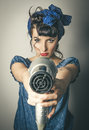 Woman in vintage clothes pointing hairdryer Royalty Free Stock Photo