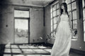 Woman in vintage creepy room a young standing by the window a derelict abandoned Stock Images