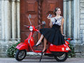 A woman in a vintage dress sitting on a scooter Royalty Free Stock Image